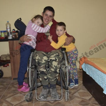 DE CRĂCIUN FII MAI BUN: Faptul că e într-un scaun cu rotile nu-l oprește să muncească și să se îngrijească de cei doi copilași