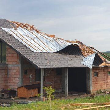 FOTO/VIDEO: O vijelie de nici cinci minute a lăsat două case fără acoperiș și a blocat un drum județean