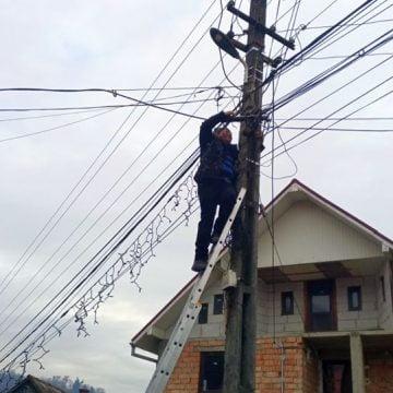 FOTO: Ca să aibă o comună împodobită, primarul s-a cocoțat el însuși pe stâlpi!