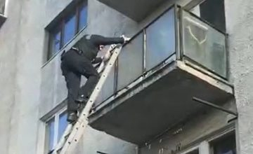 VIDEO: Intervenție la înălțime a polițiștilor, după ce o femeie a spart cu toporul ușa vecinei sale