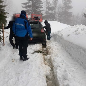 FOTO/VIDEO: Doi turiști blocați cu mașina în nămeți, în vârful muntelui, ajutați de jandarmii montani
