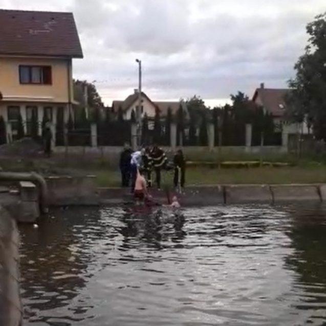 """VIDEO – Un bistrițean a încercat un """"botez"""" ad-hoc într-o baltă, dis-de-dimineață. Un polițist și un pompier l-au """"salvat"""""""